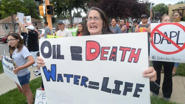 Protest organizer Kristen Kelsch hold a sign and chants across the street from the State Capitol in Bismarck on Thursday. A line of police prevented Kelsch and others from hold the protest to the Dakota Access Pipeline on the Capitol grounds