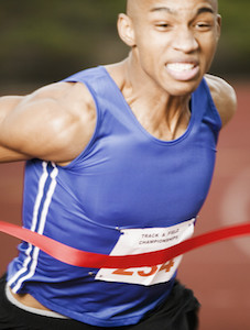 Athlete Running Through Finish Line --- Image by © Royalty-Free/Corbis