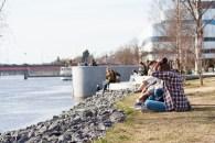 People enjoying the sun along the Ume River.