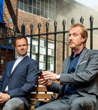 Pictured: Jonny Lee Miller (l) and Rhys Ifans (r) in CBS' Elementary. Photo: Joss Barratt /CBS ©2013 CBS Broadcasting, Inc.