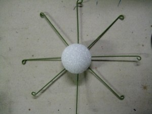"""Cut a 2"""" styrofoam ball in half, and place it, cut side down, in the center of the wires."""