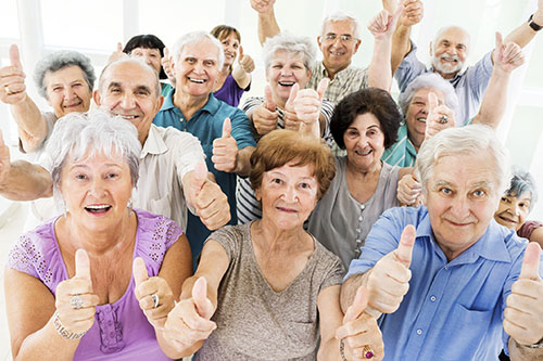 Large group of cheerful seniors showing thumbs up and looking at the camera.