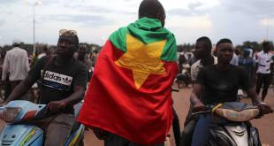 A protester wearing a Burkina Faso flag attends a protest against the presidential guard in Ouagadougou