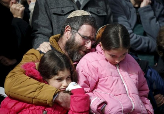 The husband and daughters of Dafna Meir, 38, mourn during her funeral at a cemetery in Jerusalem January 18, 2016. Meir, a female resident of of Otniel, was stabbed to death in her home on Sunday when an IslamoNazi broke into her house and attacked her with a knife. She died courageously defending her children.