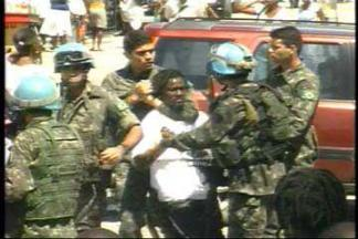 Using a chokehold, U.N. troops arrest an unarmed mourner outside the cathedral where funeral services for Father Jean-Juste had just been held. The young man has not been definitely identified but may be the popular musician Yvone Zapzap. - Photo:  2009 Haiti Information Project 