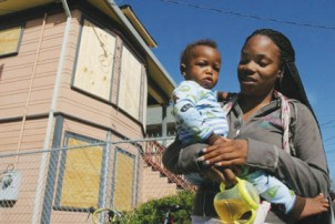 Tasha Alberti's daughter Sharquita holds her baby Zmylan Monday, July 20, outside the home she had just been evicted from after Bank of America, without warning, foreclosed, locked the family out and boarded up the windows to prevent their return. – Photo: David Bacon