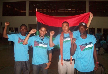"M1, shown here with young Black members of the Viva Palestina Caravan, writes in Part I: ""I felt extremely proud when the brothers got together to wave our red, black and green Liberation flag in the immigration office [at the Egyptian border] as they chanted loud enough for the people to hear us on the other side in Gaza."""