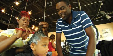 "Chris Rock watches a young girl getting her hair relaxed in ""Good Hair."""