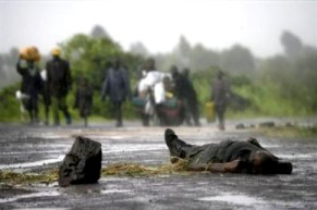 Displaced people walk past the body of a Congolese government soldier as they return home, near Kibumba, late last year.