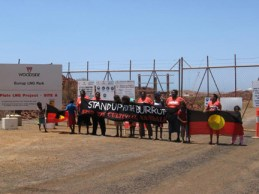 On the Burrup Peninsula, Black Australians stand bravely blocking the gates erected by Woodside, a joint venture of Chevron and Shell, to lock them out of their land. The flags the children are displaying are the Burrups own  Black for the people, red for the blood they shed trying the protect their land from settlers, yellow  and the red as well  for the ochre they use in the rock art they have been painting for at least 60,000 years.