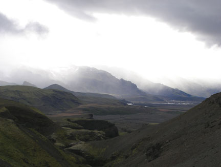 """Due to the now-familiar Icelandic Chaos (the third hut was full), we did the third and fourth legs of the trek in one day, which added up to somewhere around 25 km. After we climbed out of each ridge and valley, Páli kept saying, """"It's ok, it's all flat now,"""" but I don't think Icelanders have a very good concept of 'flat'. When we saw these mountains come out of the mist, we knew we were close to Þorsmörk, the final hut, where we could drop our packs, take off our boots, and enjoy a warm lamb and potato dinner."""