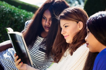 Three Christian girls studying the Bible as a group