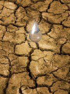 Water drop falling on parched, cracked ground. Concept for importance of water resources, breaking the drought.