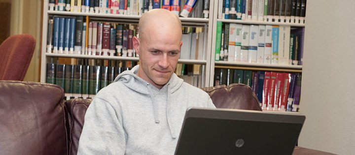 Military student in library on laptop