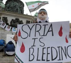 A Syrian living in Serbia displays a placard on March 16, 2013 during a protest against Syria's President Bashar al-Assad in the center of Belgrade.  AFP PHOTO / ALEXA STANKOVIC        (Photo credit should read ALEXA STANKOVIC/AFP/Getty Images)