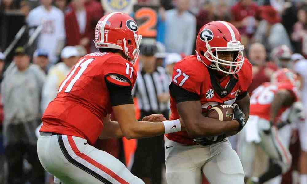 Georgia quarterback Greyson Lambert (11) hands the ball to tailback Nick Chubb (27) during Saturday's game against the Alabama Crimson Tide at Sanford Stadium on Saturday, Oct. 3, 2015 in Athens, Ga.   (Photo by John Kelley)