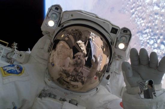 JAXA Astronaut Soichi Noguchi waves at his spacewalking crewmate, Astronaut Steve Robinson