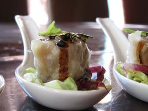a perfectly steamed shumai appetizer served on a chinese spoon
