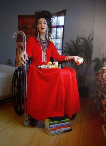 woman in a vivid red dress on a wheelchair holding a stick on her right hand