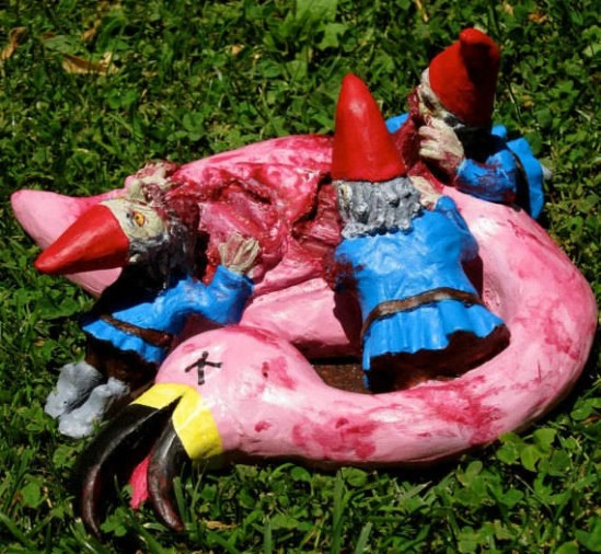 Zombie lawn-gnomes feast on a pink flamingo