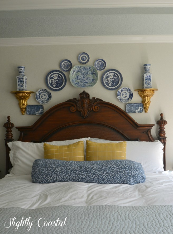 Blue and White Plates Above Bed for a Coastal Feel