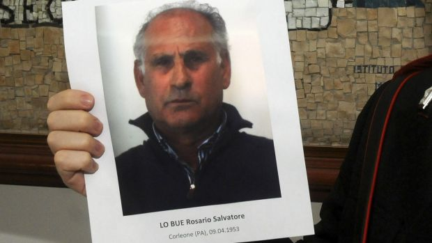 An Italian Carabiniere holds a picture of arrested Mafia boss Giuseppe Lo Bue during a press conference in Palermo, Italy, on Friday.