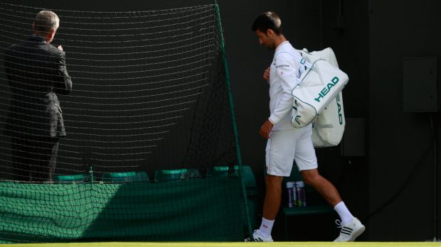 Novak Djokovic walks off at Wimbledon after his loss to Sam Querrey.