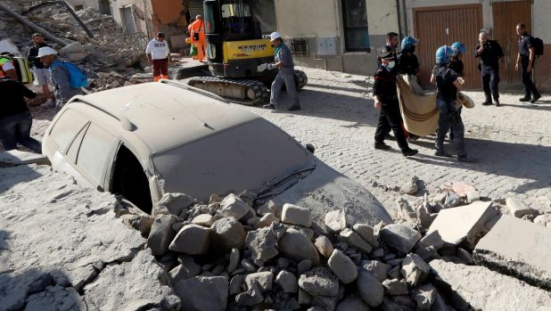 A body is carried away as a car is covered in rubble after an earthquake, in Amatrice, central Italy.