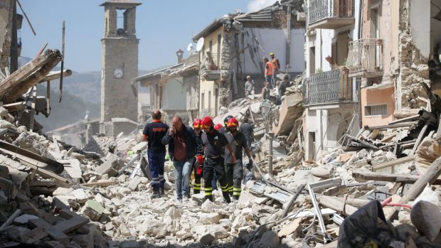 Rescue workers search for survivors in the rubble following an earthquake in Amatrice, Italy.
