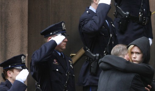 Children of slain Philadelphia police sergeant Stephen Liczbinski, Amber and Steve embrace after their father's funeral mass