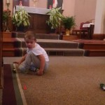 Yes, that's my boy, playing tractors in front of the altar, in his PJs, with his shoes off. I don't think Jesus minds, do you?