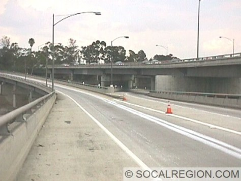 I-10 ramps over the Los Angeles River. This bridge connects I-10 westbound (right) and I-5 southbound (left) with Mateo Street and Santa Fe Avenue. Mainline I-10 runs on the bridge to the right. Vehicles visible on the bridge to the right just left I-5 southbound.