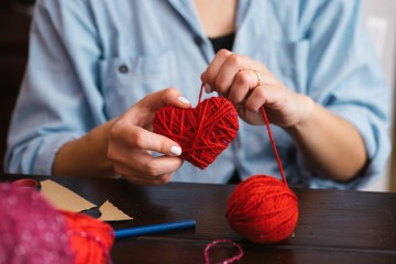 Woman creating red woolen heart