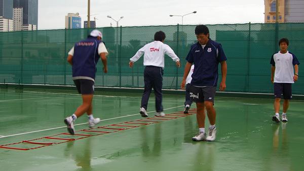 ドーハに無情の雨が降る。2006アジア競技大会大会6日目、雨中で調整する日本男子、この日は結局中止に。この大会でのソフトテニスは7日間でスケジュールされていた。