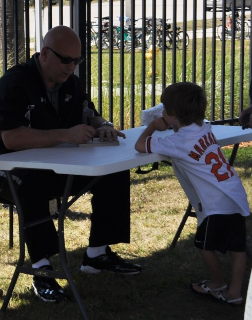 Cal Ripken, Jr. Signs an Autograph for a Young Fan at the Charlotte Sports Park, Port Charlotte, Fla., Sunday, March 10, 2013