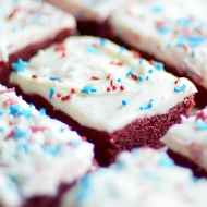 Chewy red velvet cookie bars smothered in a sweet, tangy cream cheese frosting. These bars are so easy to make since they start with a cake mix!