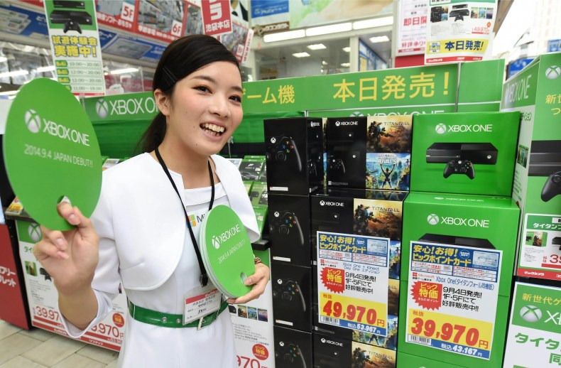 """A campaign girl for Microsoft's video game console """"Xbox One"""" promotes the console at a household appliance shop in Tokyo on September 4, 2014. Microsoft Japan launched the company's latest video game console to the Japanese market on September 4.    AFP PHOTO / Toru YAMANAKA"""