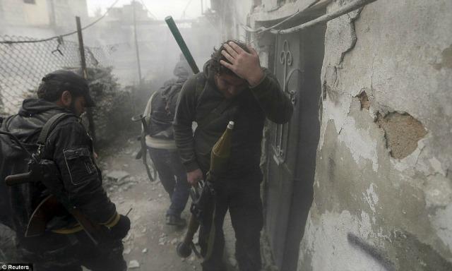 Un rebelde se toca la cabeza después de haber estado cerca de una explosión cercana.