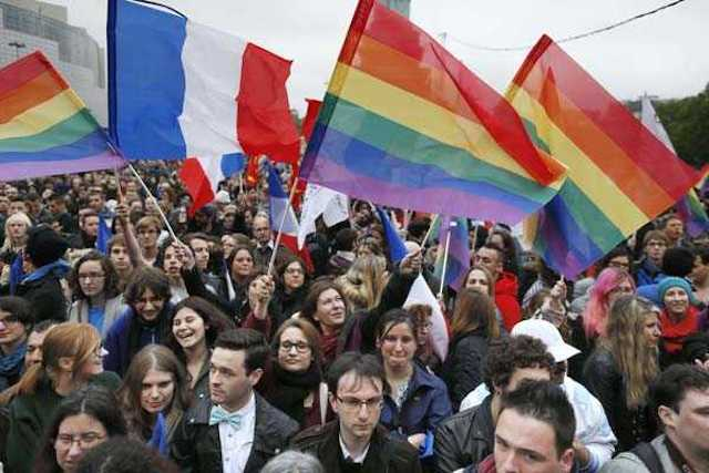 "People holding rainbow flags attend the event ""Concert pour tous!"" (Concert for all!) on May 21, 2013 at the Bastille square in Paris. The ""Concert for all!"" in reference of the French anti-gay marriage movement ""Manif pour tous !"" (Demonstration for all!), is held to celebrate the legalisation of same-sex marriage. After months of acrimonious debate and hundreds of protests that have occasionally spilled over into violence, France's National Assembly approved on April 23, 2013 a bill making the country the 14th to legalise same-sex marriage. AFP PHOTO / KENZO TRIBOUILLARD"