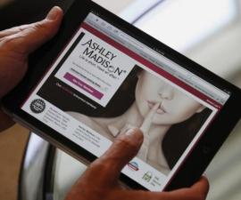 Ashley Madison founder Biderman demonstrates his website on a tablet in Hong Kong