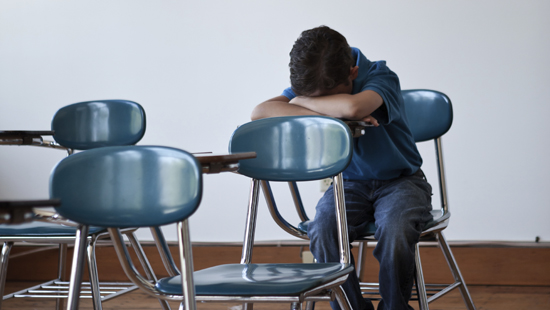 A boy alone in a classroom with his head down on a desk.