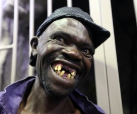 Mison Sere smiles after winning the 2015 edition of the Mr Ugly competition, in Harare, Saturday, Nov. 21.2015. Sere who controversially dethroned  former Mr Ugly William Masvinu to scoop the top prize of $500  in a contest marked by allegations of cheating. Masvinu has had  it relatively easy over the past 3 years when the contest struggled to draw more than 10 contestants. This year's competition attracted  35 contestants with organisers saying they were looking for  people with natural ugliness. (AP Photo/Tsvangirayi Mukwazhi)