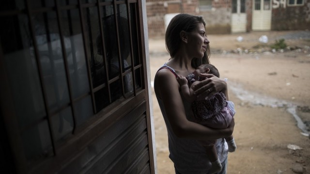 In this Dec. 22, 2015 photo, Angelica Pereira holds Luiza outside their house in Santa Cruz do Capibaribe, Pernambuco state, Brazil. Luiza was born in October with a rare condition, known as microcephaly. The Zika virus, first detected in humans about 40 years ago in Uganda, has long seen as a less-painful cousin to dengue and chikunguya, which are spread by the same Aedes mosquito. Until a few months ago, investigators had no reported evidence it might be related to microcephaly. (AP Photo/Felipe Dana)