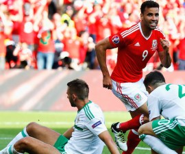 PARIS, FRANCE - JUNE 25:  Hal Robson-Kanu (C) of Wales celebrates his team's first goal while Gareth McAuley (L) of Northern Ireland shows his dejection during the UEFA EURO 2016 round of 16 match between Wales and Northern Ireland at Parc des Princes on June 25, 2016 in Paris, France.  (Photo by Clive Rose/Getty Images)