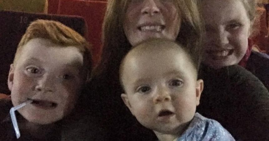 PIC BY MERCURY PRESS (PICTURED: A GHOST APPEARING OVER THE SHOULDER OF EMMA JOHNSON, 35, AT THE CINEMA WITH HER CHILDREN GEORGE, 6, HARPER, 7 MONTHS AND AVA, 8) An unsuspecting family were photobombed by a ghost girl holding a teddy bear while they posed for a spooky selfie in an empty cinema screen. Emma Johnson, 35, from Liverpool, waited for the screen at the Light Cinema in nearby New Brighton to empty before taking a snap with George, six, Ava, eight and first-time cinema-goer seven-month-old Harper. But the family, who were watching new Disney Pixar flick Finding Dory, discovered that they were not on their own and instead appeared to be stalked by a spectral figure when they checked the photo back at home. SEE MERCURY COPY