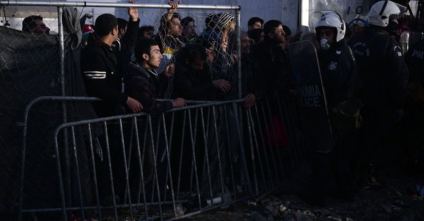 Migrants and refugees stand at the gate of the Greek-Macedonian border, near the Greek village of Idomeni, on March 2, 2016, where thousands of people are stranded. The EU on March 2 proposed 700 million euros in emergency aid for Greece and other states as it began to tackle the migrant crisis within its borders like humanitarian disasters in developing countries. The United Nations has warned of a looming humanitarian crisis as thousands of people remained stuck in miserable winter conditions on the Greece-Macedonia border after Balkans states and Austria capped the numbers arriving.