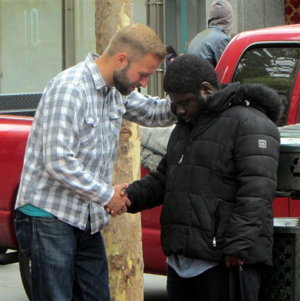 CAL PRAYS WITH MAN AT 5TH AND MARKET.