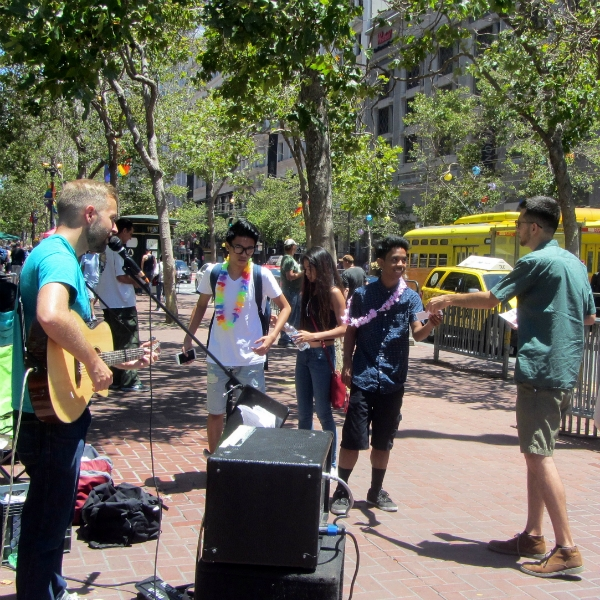 CAL SINGS AND JACOB PASSES OUT TRACTS AT 5TH AND MARKET. THE RAINBOW NECKLACES ARE FOR GAY PARADE.