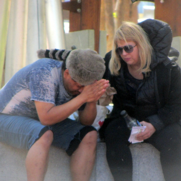 DEANNA PRAYS WITH MAN AT UN PLAZA.