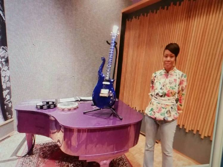 Tammy Sharpe standing in front of one of Prince's pianos and guitars at Paisley Park.